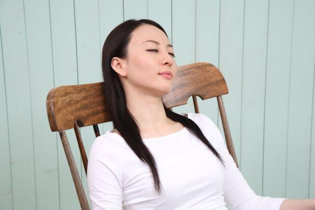 椅子に座って目を閉じる女性